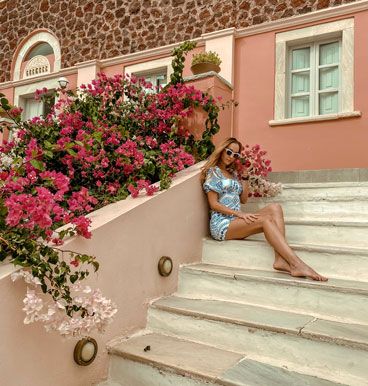 julia atravelgirl in front of a pink house near pink flowers in oia